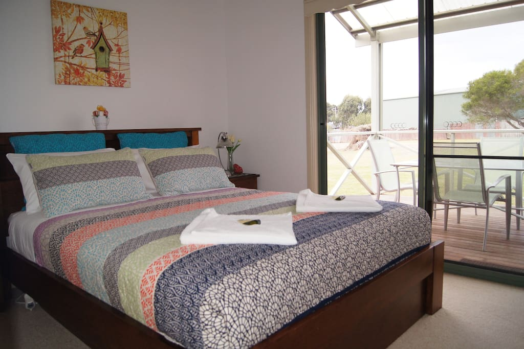 Bedroom with queen size bed, comfortable bed, sliding door to decking and sealing fan