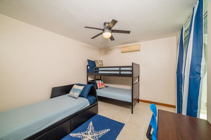 The Guest Bedroom has one twin bed and bunk beds, for a total of 3 twins. It also has air conditioning, a small private balcony, and a writing desk with chair to accommodate any work or school needs.
