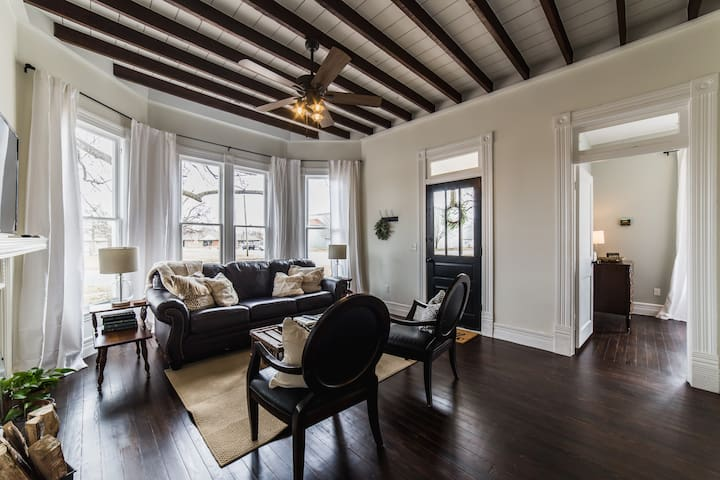 Living room features bay window and original beamed ceiling.