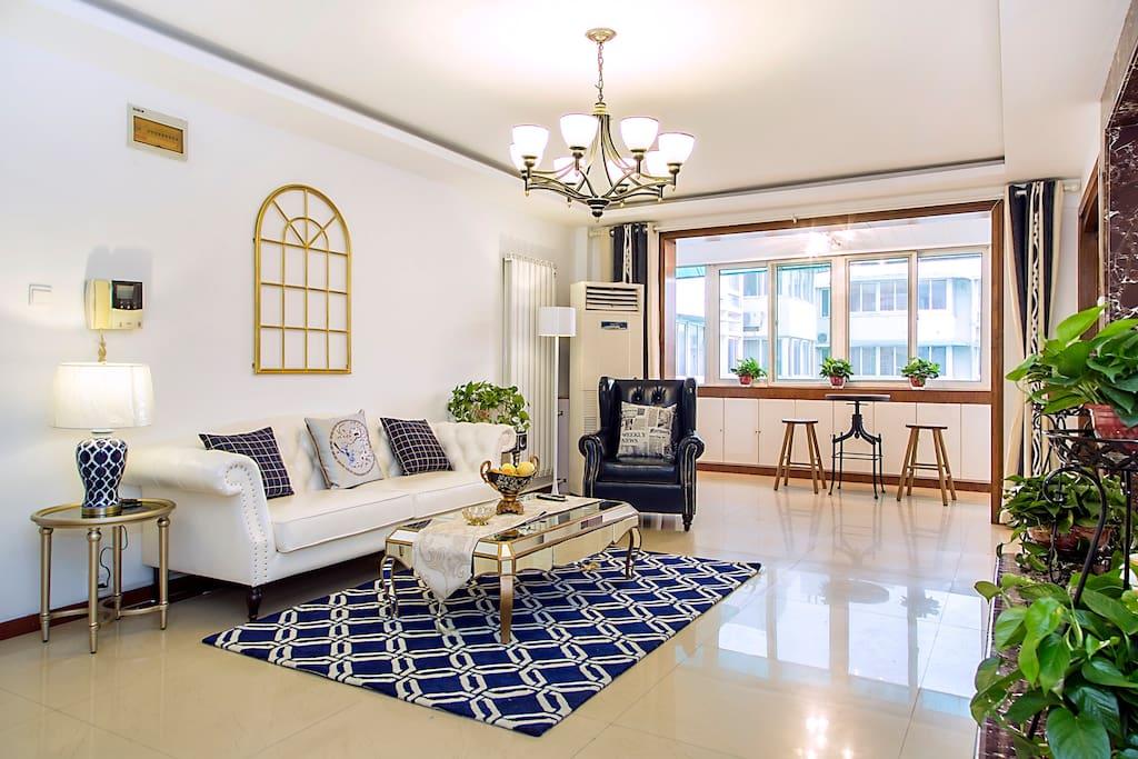 客厅配备高档家居和家电,打造出高贵,典雅的气息,宝石蓝色的地毯和金属边框让整个空间充满了法式浪漫气息