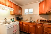 Full size stove, refrigerator, microwave, tea kettle, coffee pot, and more in the kitchen.