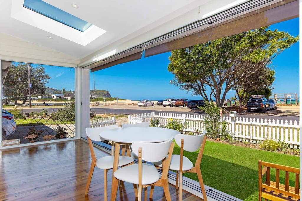 Casual dining table with doors opened up the the sands and headland of Avoca Beach