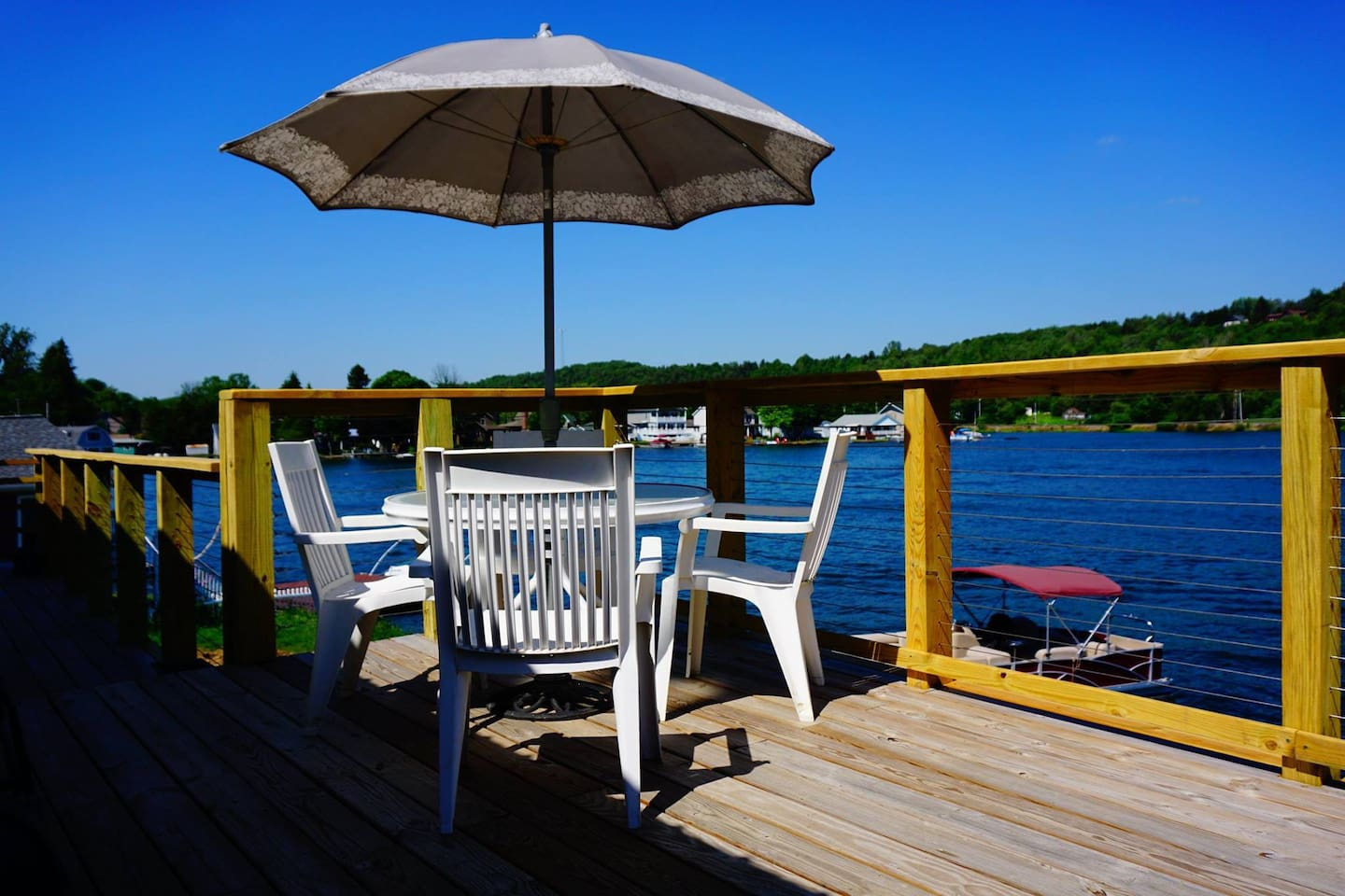 A TWELVE BY FIFTY FOOT DECK WITH TABLES AND CHAIRS AND GRILL