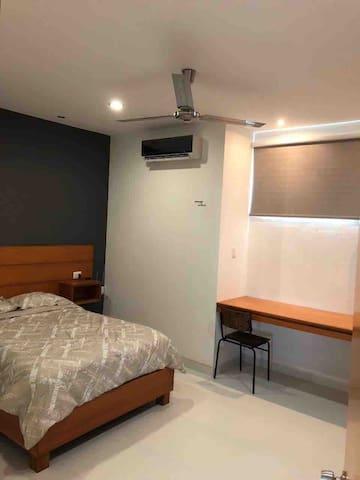 Recámara cama matrimonial, ventilador de techo clima y escritorio de trabajo