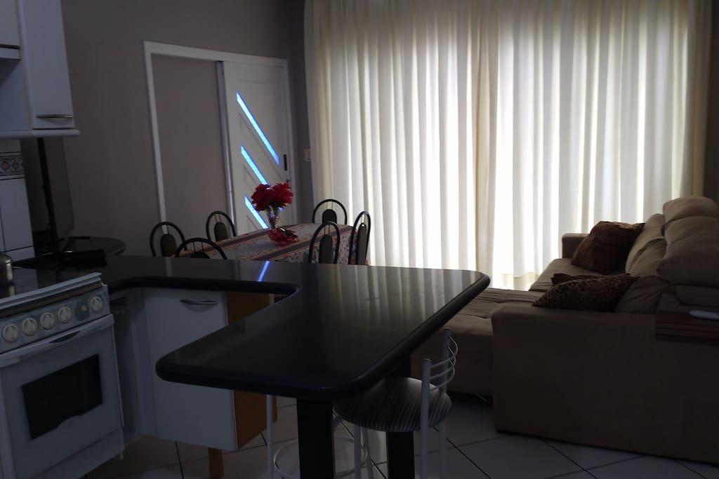 Cozinha e sala, com refrigerador, pia, fogão, bancada mesa, sofá cama e tv a cabo.