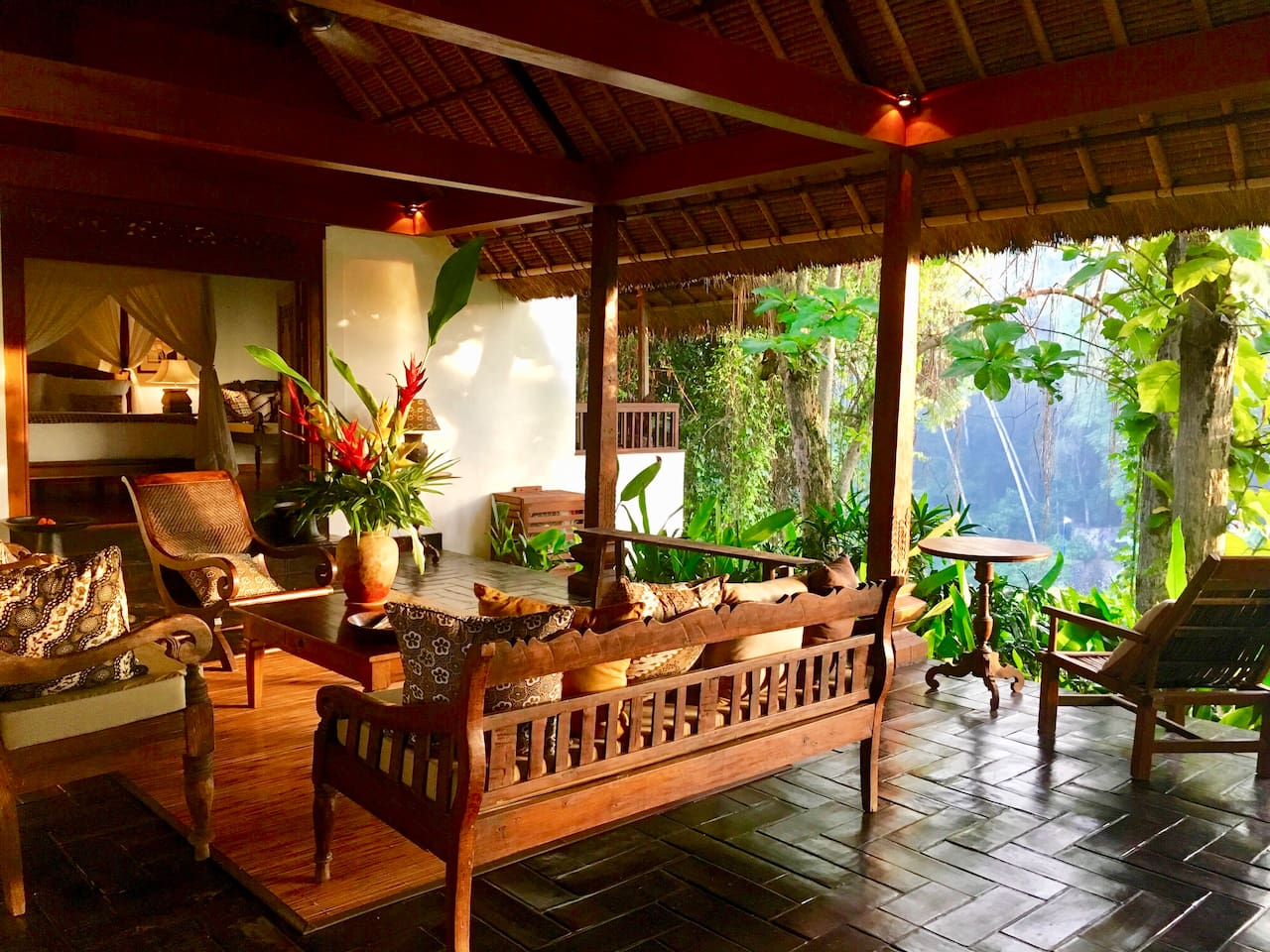 The stunning wantilan (living pavilion) with its tranquil views across  the River Penet, through the lush green foliage,  to the beautiful Balinese temple opposite