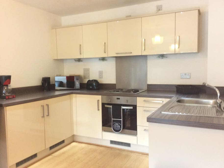 Kitchen with dishwasher,coffee machine,toaster and microwave oven.
