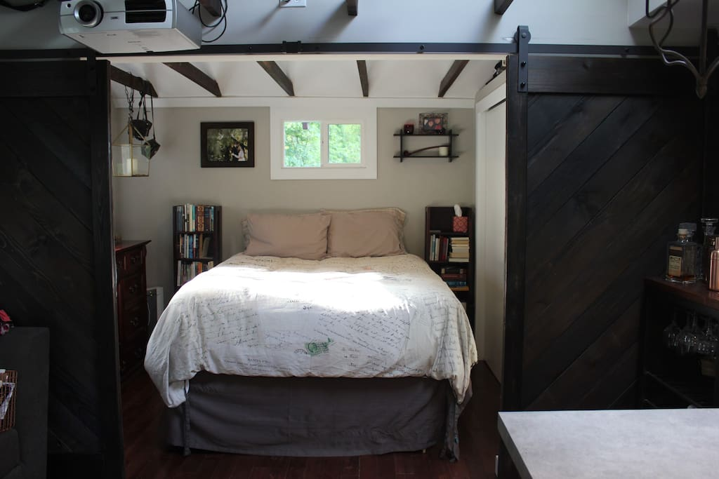 Behind sliding barn doors is the comfortable queen bed, with lofted ceilings and a designer fan.