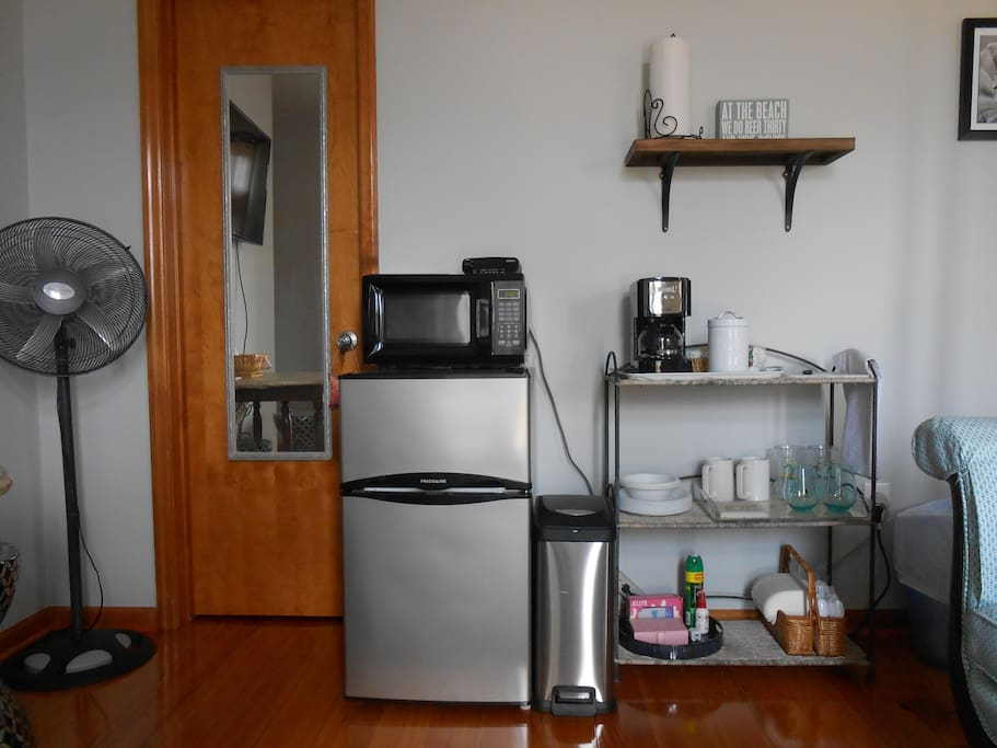 Kitchen area with coffeemaker, microwave, & fridge with separate freezer.