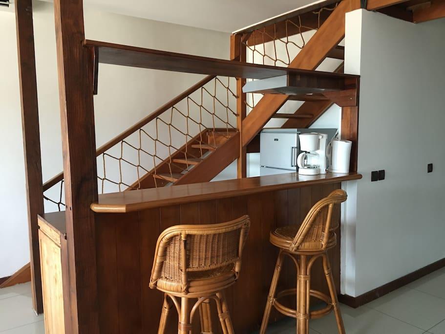 Le bar, le coin cuisine et l'escalier vers l'étage des chambres