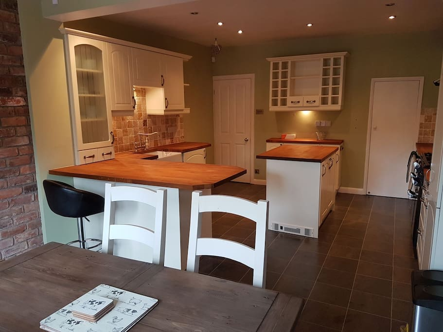Large kitchen diner with breakfast bar leading onto garden