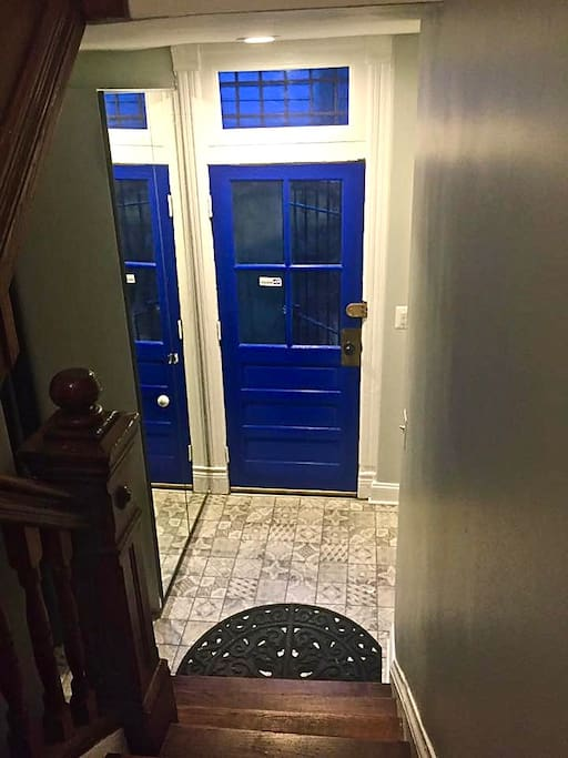 The topmost apartment in a three unit home is accessed through the side entrance, but even here you enter in style with a cobalt blue door and a printed ceramic entryway.
