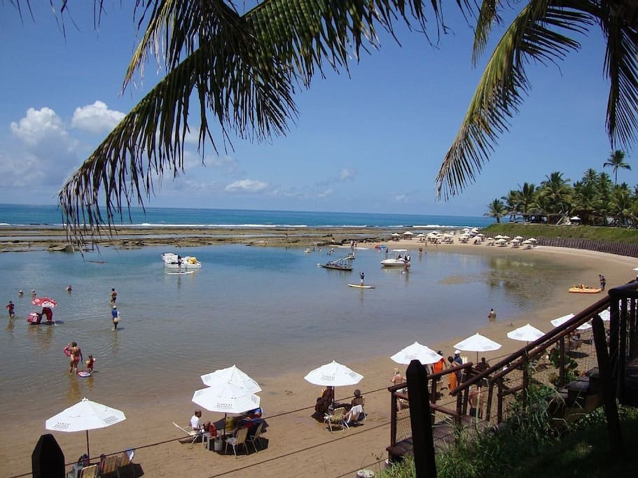 Praia em frente ao Flat, com sombreiros, cadeiras e serviço do restaurante disponíveis