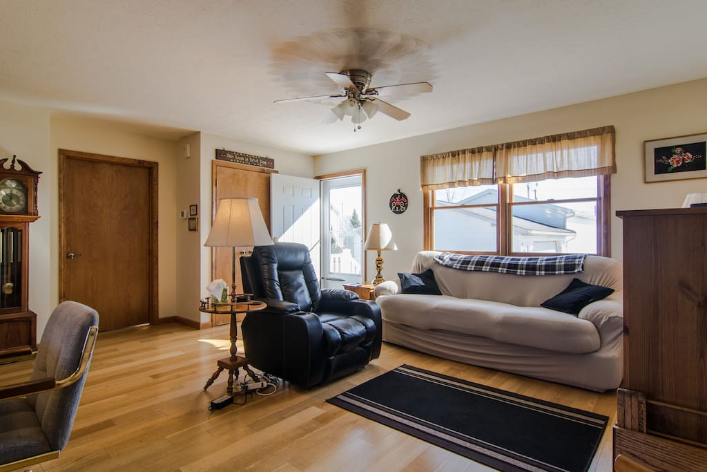 Sunny and bright living area with electric reclining chair and comfortable couch.