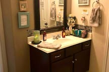 Attached 1/2 bath downstairs with full bath located upstairs. All bathrooms are shared