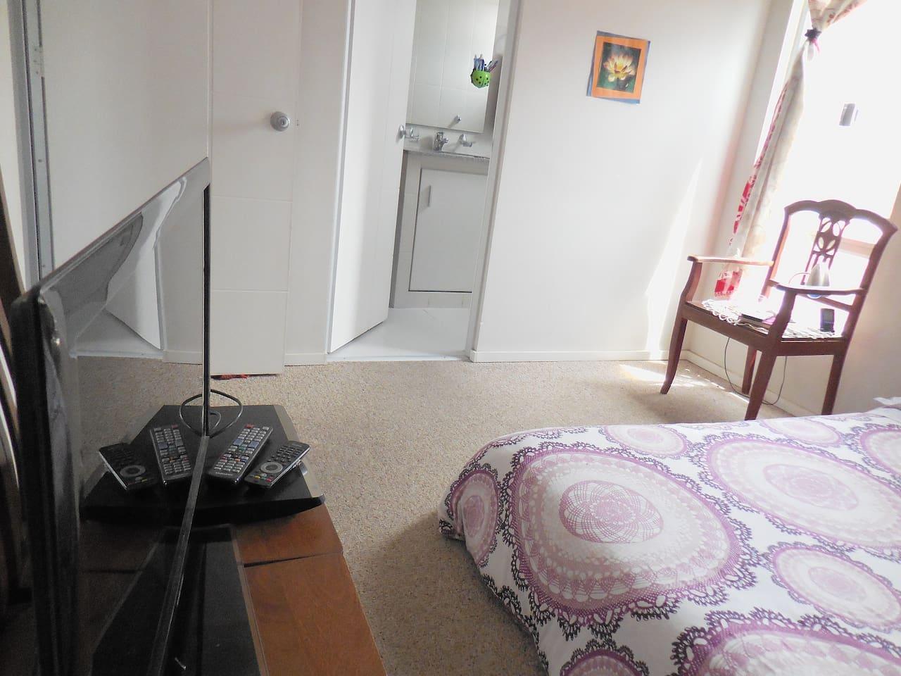 Habitación 1: Moderna e iluminada, con baño privado y televisión.