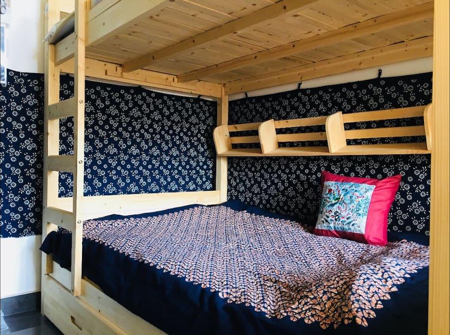 纯实木上下铺温馨舒适。床罩墙罩全部手工蓝印染、扎染等布艺。