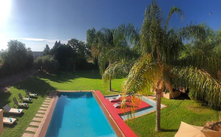 Vue d'ensemble du jardin et la piscine depuis le balcon à l'étage