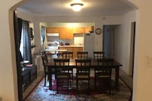 Large dining room table with nautral light  and kitchen bar.