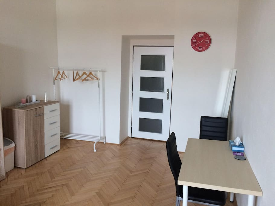 table, clothes rack and cabinet in the room
