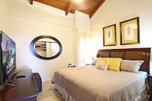 Master bedroom features a comfy hotel-quality King-size bed, large flat screen TV, air conditioner, and ceiling fan