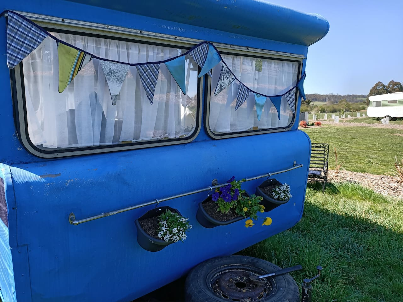 Blue is a Wayfarer 1970's 14ft Caravan, she has the biggest bed in all our onsite vans which is a comfortable queen bed (inner sprung mattress), a small double bed (fold down foam, formed from dining seating booth) and a dining booth. She comes equipped with a sun lounger, picnic rug and picnic basket, all linen and towels are provided.