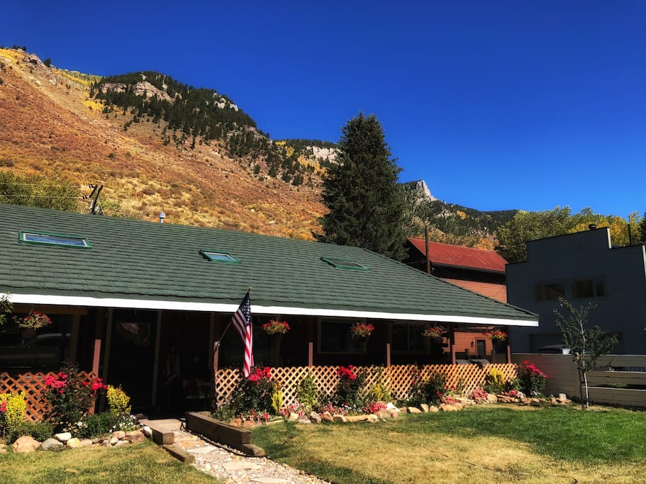 Exterior photo of our house, shot during fall, with lions head framed in the cliffs behind the house
