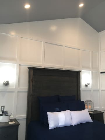 Queen Size Wood Farm House Head Board & Foot Board Gray Color New Pillow Top Mattress 2 Sconces by each Farm house night stands with dimmer lighting.  Another 2 sconces by the flat screen T.V. Shaker wall Wainscoting through out the Guest House