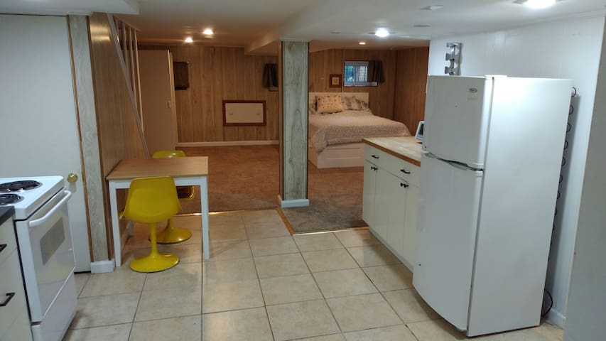 Basement suite with queen bed, wardrobe, desk, sitting area and kitchenette.