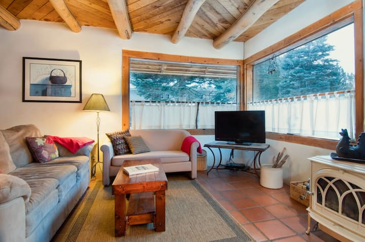 NM Safe Certified Cleaning. Cozy log cabin with wood stove near mountain stream