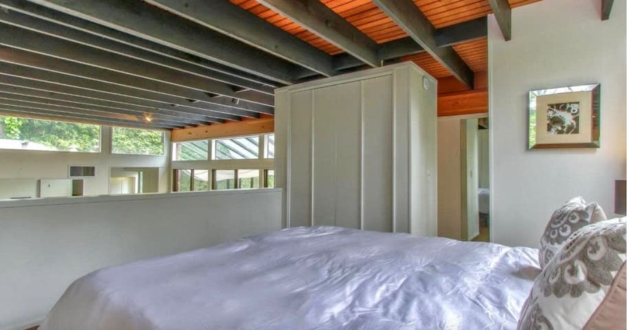 The main level's loft upstairs bedroom has an open half-wall that overlooks the Great Room below.