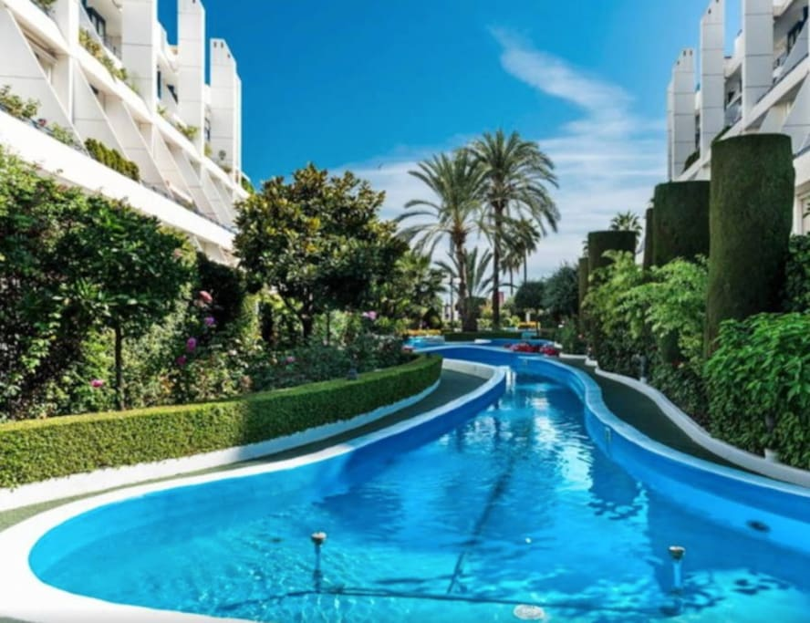 Lush surroundings of manicured gardens, fountains and pools features throughout the complex