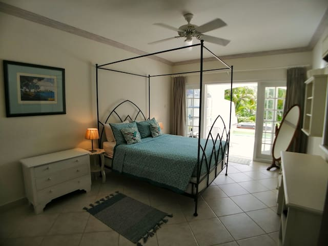 Bedroom 2 has a queen bed, overhead fan and aircon, en suite bathroom and doors leading to the pool and jacuzzi