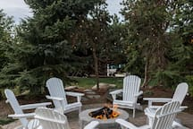 Outside patio area with chairs and fire pit in a cove of evergreens.