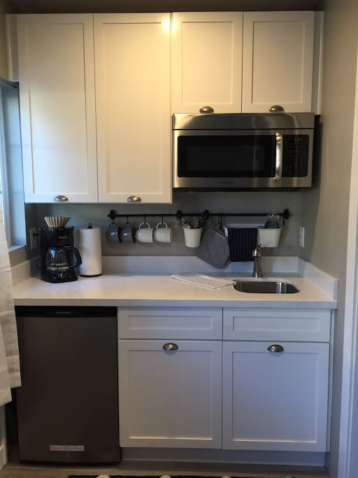 Kitchenette stocked with coffee, dishes with sink and microwave.