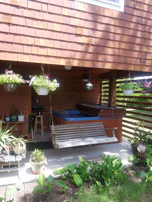 Swing bench and nags head hammock chair between hot tub and flower garden.