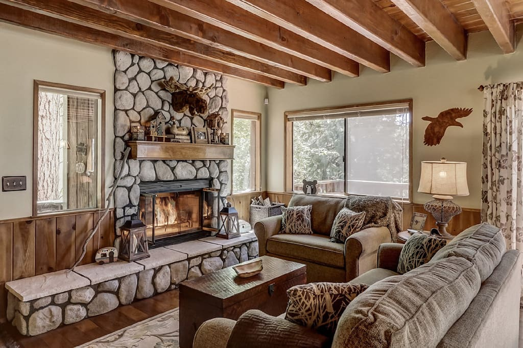 Open Living Room with River Rock Fireplace with Beautiful Forest Views