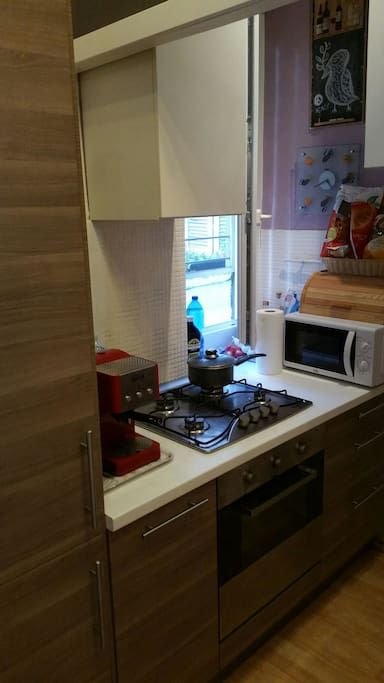 Kitchen with stove, microwave, professional machine for coffee and cappuccino