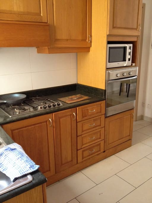 In the kitchen there is a gas cooker, oven, microwave and an electric kettle.