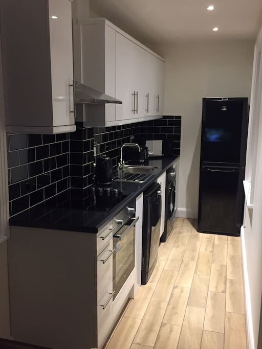 Compact kitchen with cooker, hob, fridge/freezer, washing machine and dishwasher.