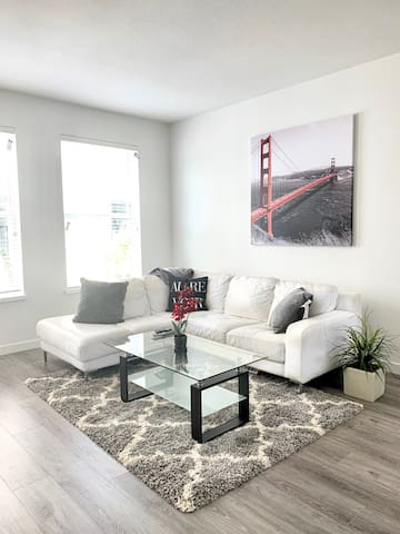 """Spacious living room with a faux leather couch equipped with a 60"""" cable tv and access to amazon, YouTube, Netflix etc."""