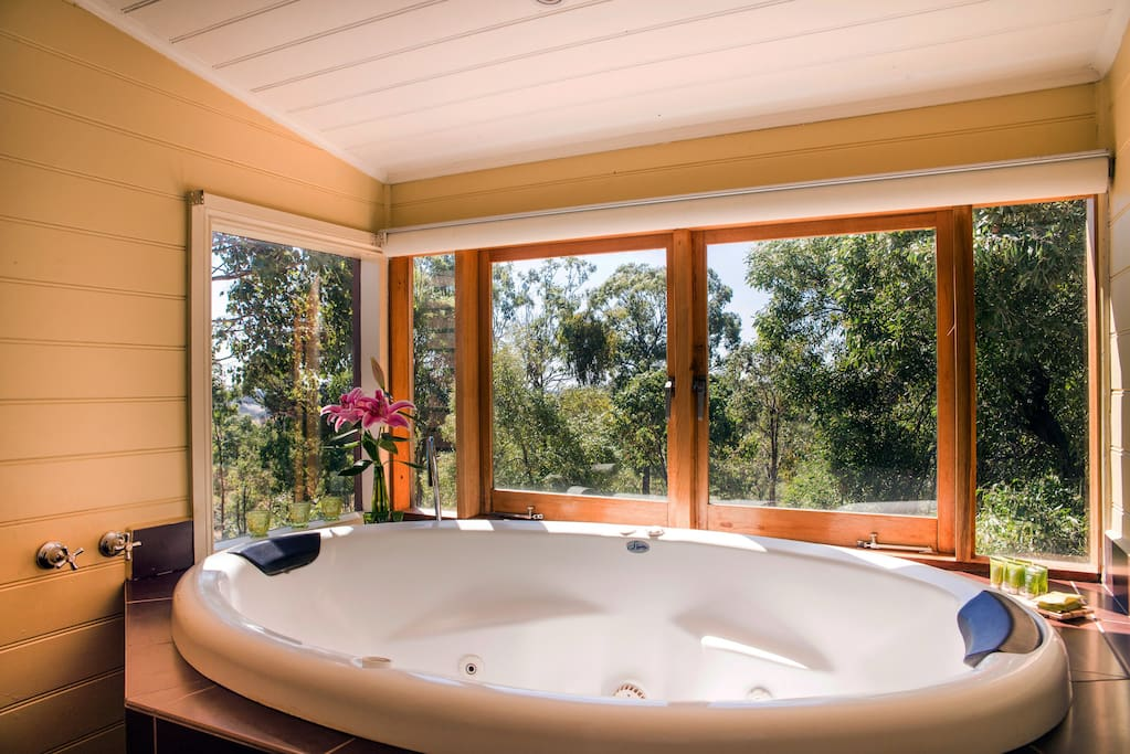 Indoor two person spa bath with views of the countryside