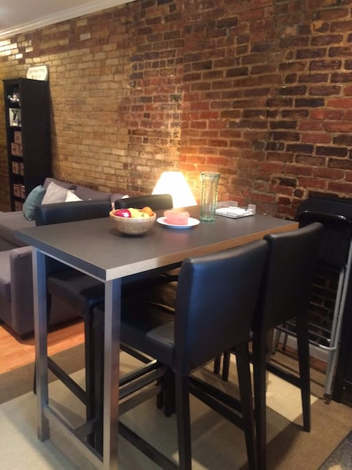 Dining table space that can seat up to 4 guests, with 3 additional folding chairs available.