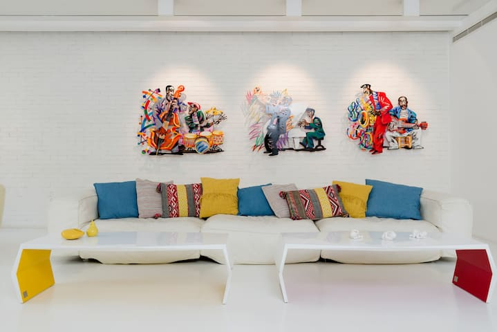 The white furniture is contrasted with the colorful and quirky pillow covers and one-piece artworks.