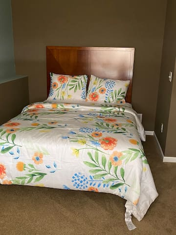 Basement bedroom  with queen bed  near a full bathroom and laundry