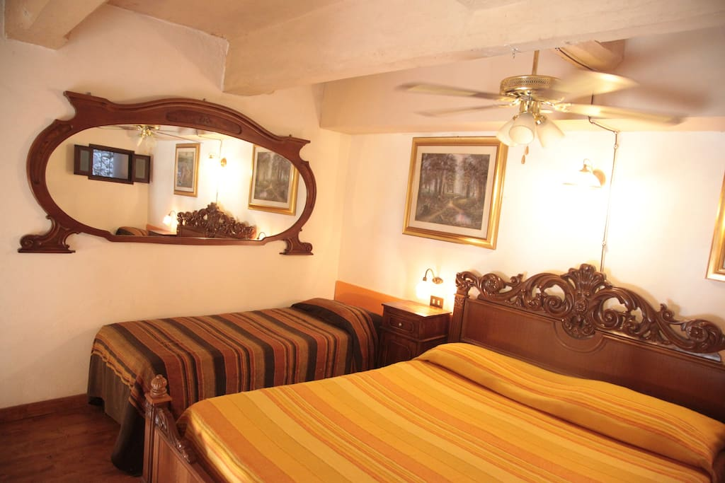 Upstairs: confortable sleeping loft with 1 double bed. 2 single beds, wardrobe, ceiling fan and small window.