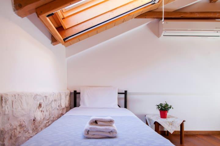 Μερική άποψη από τον χώρο του ύπνου , με το ένα από τα δυο μόνα κρεβάτια και το παράθυρο οροφής
