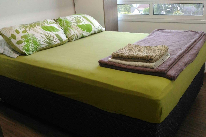 Quarto completo com cama de casal, travesseiros e toalhas de banho