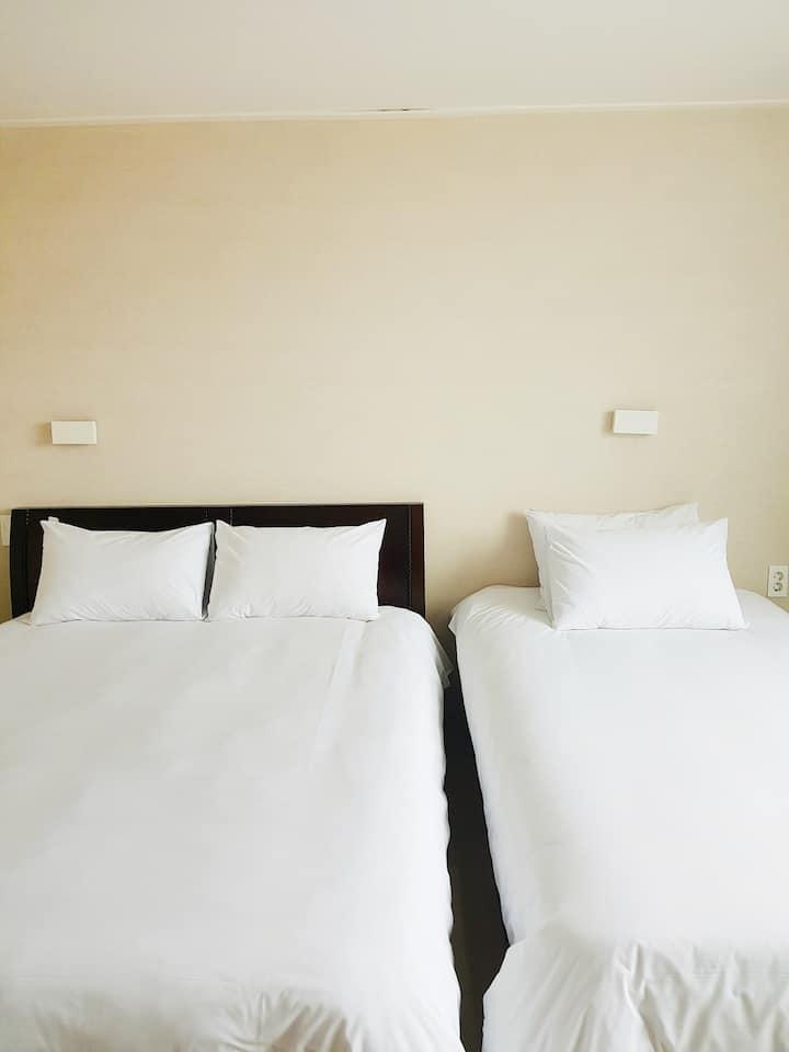 침대 2개가 준비되어 있는 깔끔한 화이트톤 인테리어의 301호(DELUXE TWIN)