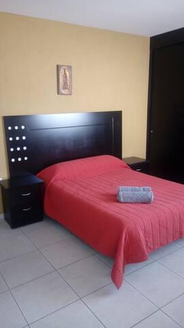 Dormitorio con cama matrimonial, tocador y closet.
